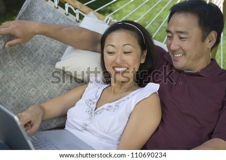 Happy asian couple using laptop while lying on hammock - stock photo