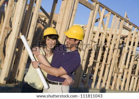 Happy asian couple with blueprint at construction site