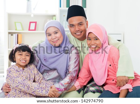 Happy Asian family at home. Muslim family having fun indoors. Southeast Asian parents and children smiling. - stock photo