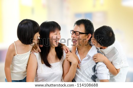 Happy Asian family at home sharing their story - stock photo