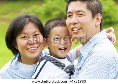 Happy Asian family at outdoors - stock photo