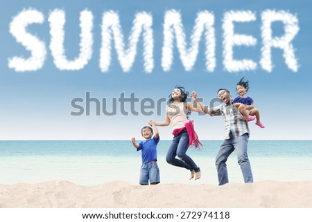 Happy asian family enjoy holiday and jumping on the tropical seashore under a summer's cloud - stock photo