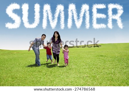 Happy asian family enjoy vacation together and running on the green meadow under a summer's cloud - stock photo