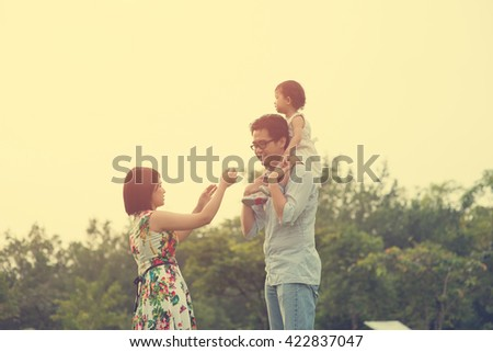 Happy Asian Family enjoying family time together in the park vintage tone