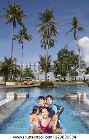Happy Asian family having a good time at swimming pool - stock photo