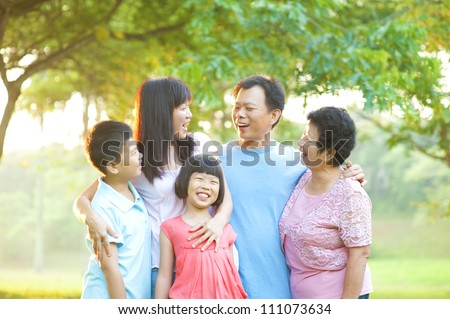 Happy Asian family having conversation at outdoor - stock photo
