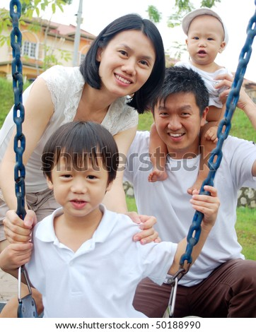 happy asian family having fun at playground