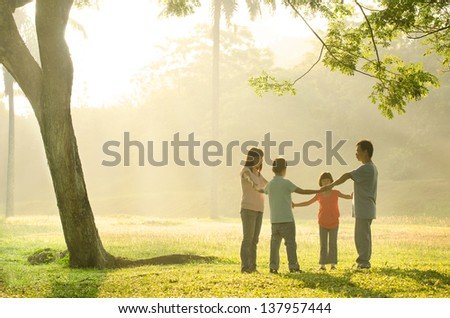 happy asian family having quality time playing in the outdoor green park during a beautiful sunrise - stock photo