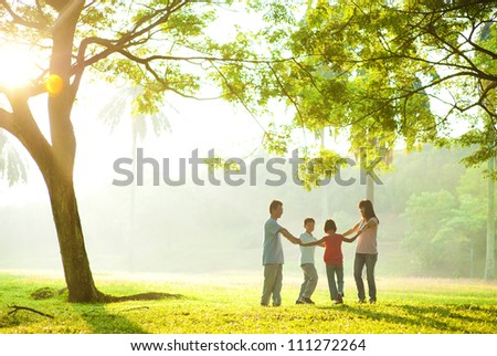 Happy Asian family holding hands in a circle and running over green lawn - stock photo