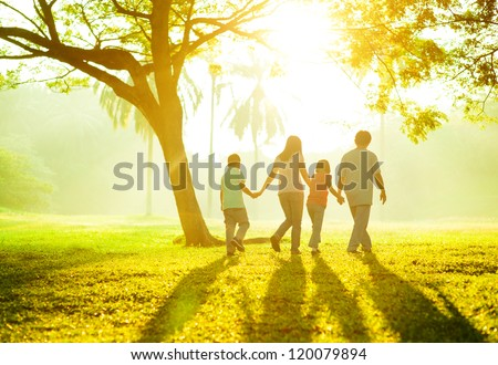 Happy Asian family holding hands walking over green lawn outdoor park, having quality time together. - stock photo