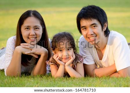 Happy Asian family in park - stock photo