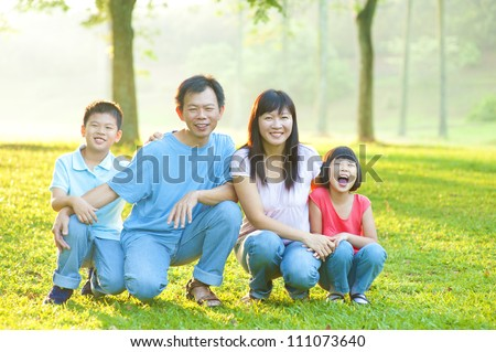 Happy Asian family in the park - stock photo
