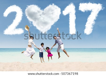 Happy Asian family jumping together on the beach while holding hands with cloud shaped numbers 2017