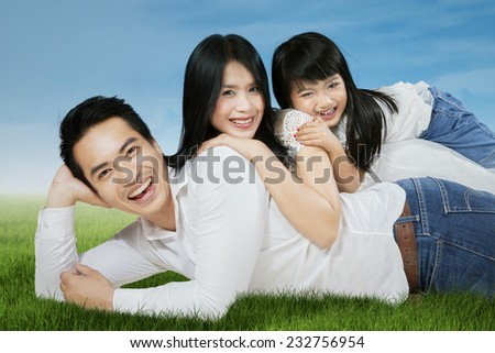 Happy asian family lying on grass and looking at camera, shot outdoors - stock photo