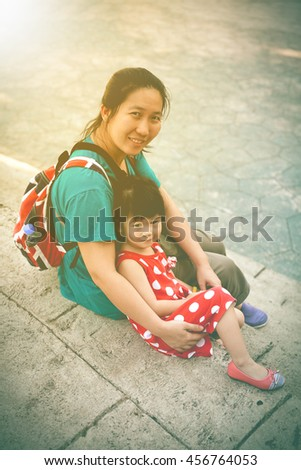 Happy asian family, mother and lovely daughter smiling and looking at camera. Playful child and parent relaxing outdoors in the day time with sunlight, travel on vacation. Vintage tone.