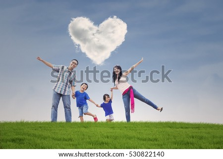 Happy Asian family of four with heart shaped cloud