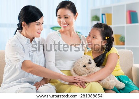 Happy Asian family of three stacking hands - stock photo