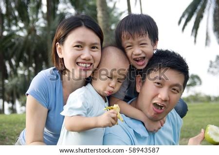 Happy asian family on picnic - stock photo