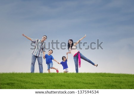 Happy Asian family on the green hill