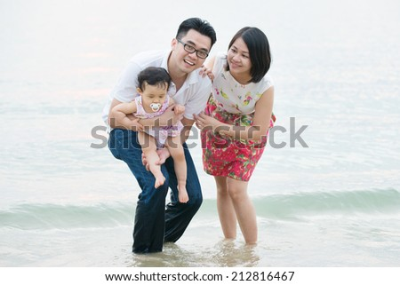 Happy Asian family outdoor on sand beach, vacation during summer, natural sunset sunlight.