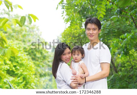 Happy Asian family outdoor. Portrait of parents and child having fun at garden park on weekend. - stock photo