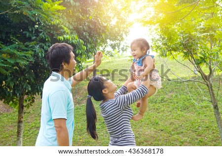 Happy Asian family playing in park during summer sunset, outdoors shot. - stock photo