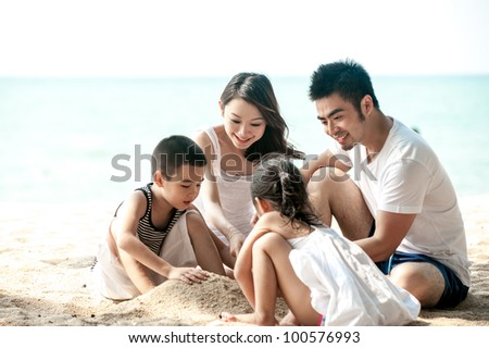 Happy Asian Family Playing on the beach