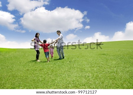 Happy asian family playing on the field. They are running in circle shot over blue sky