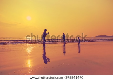 Happy Asian family playing together on tropical beach at sunset time for holiday or summer background