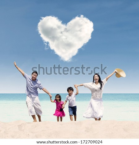 Happy Asian family run at beach under love cloud - stock photo