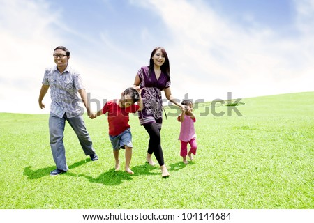 Happy Asian family running together in meadow shot outdoor - stock photo