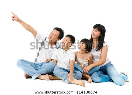 Happy Asian family sitting on floor and pointing over white background - stock photo