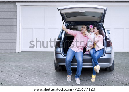 Happy Asian family taking selfie photo together with a smartphone while sitting in the open car baggage