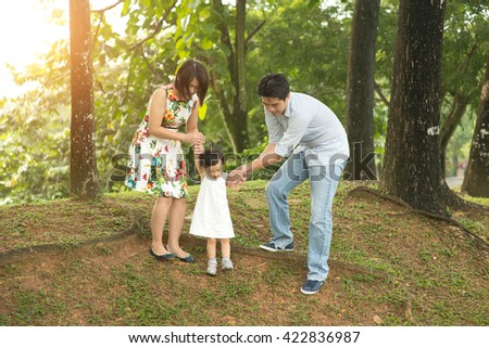 happy asian family walking on the park