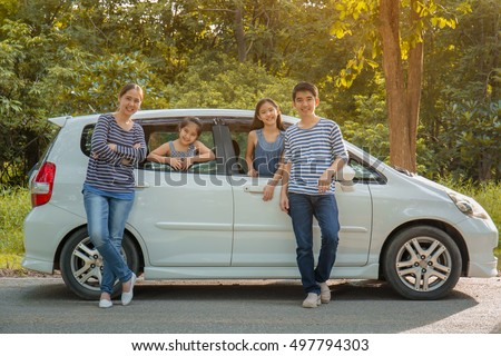 Happy Asian family with mini van are smiling and preparing for travel on summer