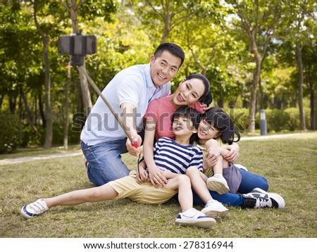 happy asian family with two children taking a outdoor selfie with selfie stick outdoors in a city park. - stock photo