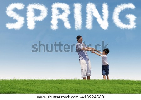 Happy asian father holding hands with his son on the green meadow under a spring cloud