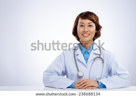 Happy Asian female doctor sitting at the desk, isolated on white background - stock photo