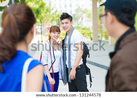 Happy asian friends outdoors smiling and looking at camera - stock photo