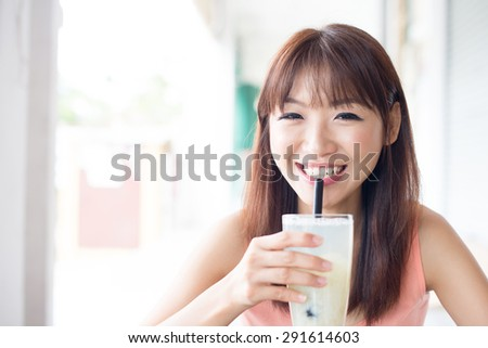 Happy Asian girl drinking a glass of beverage with straw in cafe. Young woman living lifestyle.