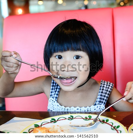 Happy Asian Girl eating in the restaurant - stock photo