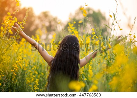 Happy Asian girl feeling freedom in the flower field, Freedom concept - stock photo