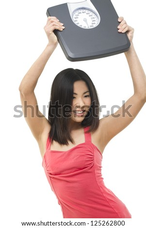 Happy Asian girl holding up a weight scale above her head