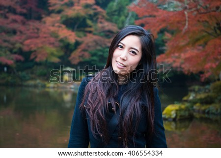 Happy Asian Girl in a park during Autumn season. Portrait of a young Asian woman with autumn trees and a lake on the background. Woman portrait in a park in Autumn Season