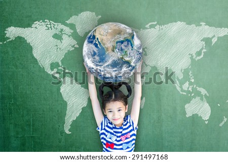 Happy Asian girl kid child raising hands holding globe on green chalkboard with world map background: Children's education for world literacy day concept : Elements of this image furnished by NASA   - stock photo