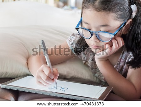 Happy Asian girl kid enjoy using pen on tablet smart technology gadget pc pad device drawing freehand doodle leisure art on fun free time: Little school child draw cartoon pro innovative touchscreen