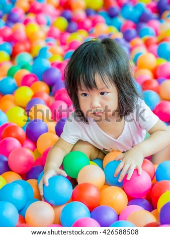 Happy Asian girl playing with balls