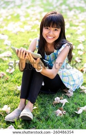 Happy asian girl sitting on grass with tablet computer looking at camera - stock photo
