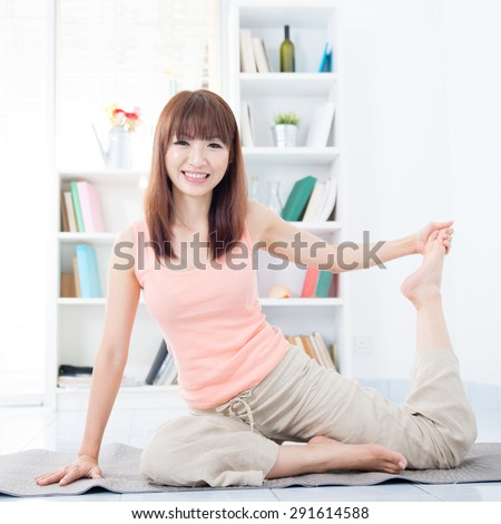 Happy Asian girl stretching and yoga in the morning. Young woman indoors living lifestyle at home. - stock photo