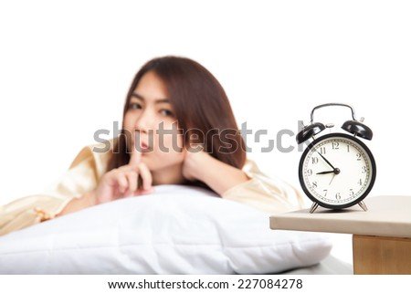 Happy Asian girl  wake up show quiet sign  with alarm clock  isolated on white background - stock photo